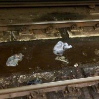 Trash floating in pooled water between the tracks