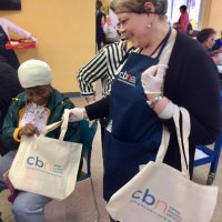 During lunch, Lisa Fernandez hands out free Carter Burden Network canvas bags.