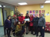 Lisa Fernandez (in red), Outreach Director Hallie Shapiro and Case Worker Yulisa Santana accept a donation from the Popup Market Committee.