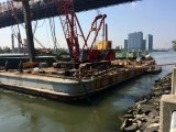 Barges prepare the waterfront in preparation for arrival of the landing. Construction on the LIC site can be seen in the background.