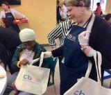 On a typical day of service to Roosevelt Island seniors, Lisa Fernandez offers lunch and free tote bags at the CBN/RI Senior Center