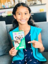 Maya Rodney shows off the Girl Scout Cookies box with her on the cover.