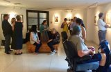 Artists and visitors mingle at a recent art exhibit curated by RIVAA, favorites to win RIOC's Artist-in-Residence Grant