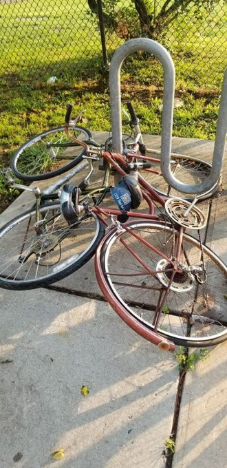 Collapsed on their sides, two abandoned bikes celebrate a first anniversary of eating up rack space near Firemen's Field.