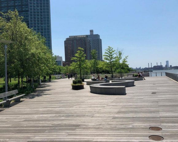 Gantry State Park's boardwalk with abundant seating with skyline and river views.