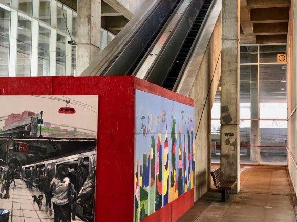 A plywood shed, painted Roosevelt Island red, murals added, fails to hide a once useful escalator RIOC refuses to repair.