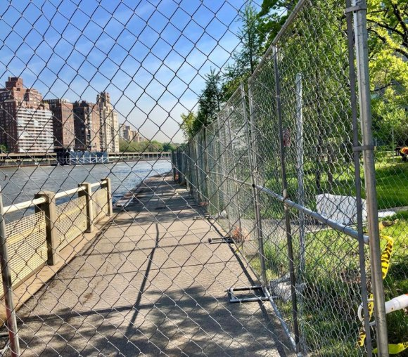 Protective fencing restricting access to the West Promenade during seawall railing construction will remain until the work is done.