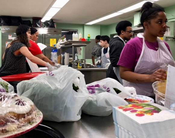 Teens from Moving Forward's cooking class, taught by Nia Bailey, practice what they've learned, catering a packed cafeteria at the Senior Center.