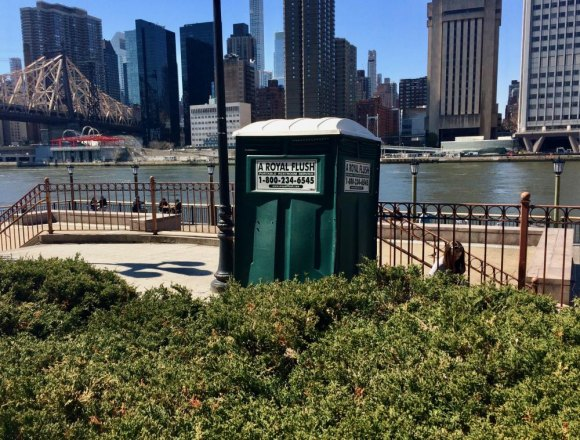 Modern day outhouse and scenic skyline make strange partners.