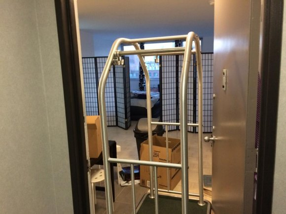 Manhattan Park transient apartment door propped open with luggage cart, community values not included.