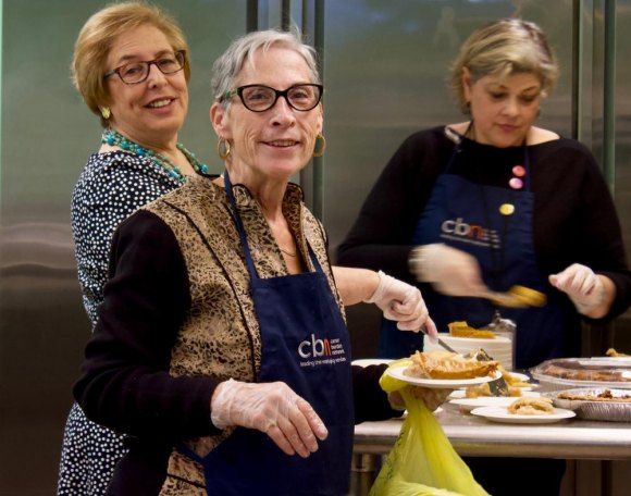 What CBN does: Volunteers, including director Lisa Fernandez, serve free meals to the needy on holidays.