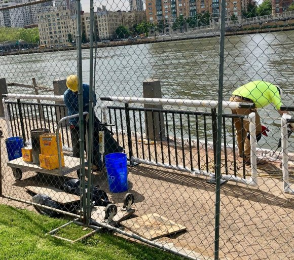 A crew is busy working on new seawall railings before crowds begin walking up to Lighthouse Park for FIGMENT NYC 2019.