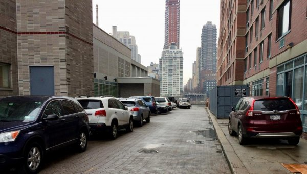 Cars parked free continue to choke the alley beside PS/IS 217