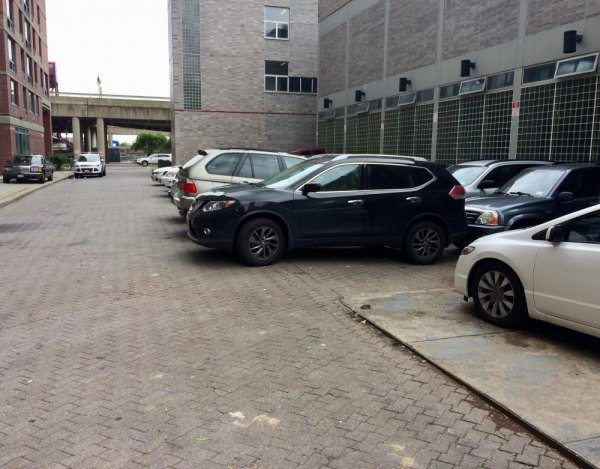 Illegal parking on Tuesday at PS/IS 217, crossing the line into the fire lane. Garbage that drew rats all weekend was moved to make space for the white car parked on the right.